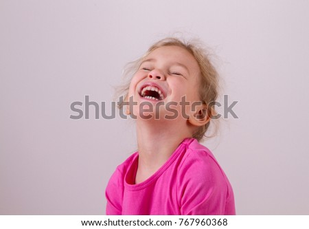 cute little girl bursts into laughter, laughs heartily on white background #767960368