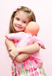 Cute little girl child holding and embracing her doll isolated