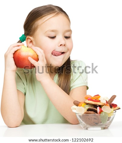 Cute little girl choosing between apples and sweets licking her lips, isolated over white
