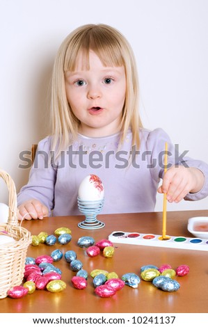Cute Little Girl Decorating A Basket of Easter Eggs