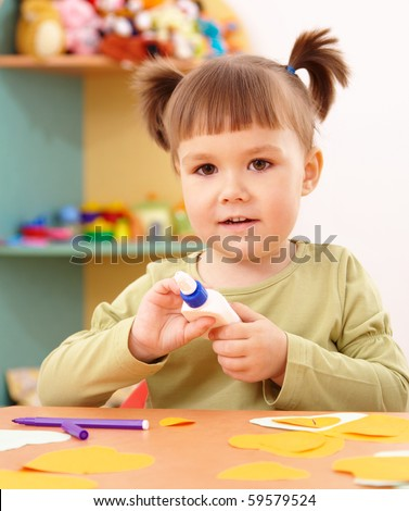 Cute little girl doing arts and crafts in preschool
