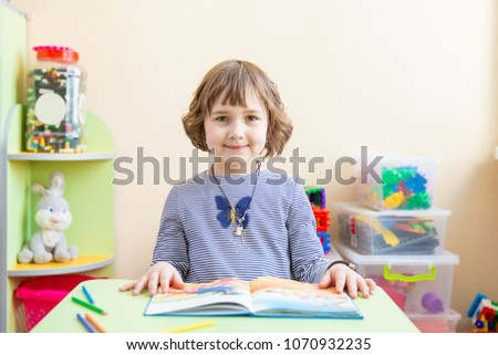 Cute little girl doing homework, reading a book, coloring pages, writing and painting. Children paint. Kids draw. Preschooler with books at home. Preschoolers learn to write and read. Creative toddler #1070932235