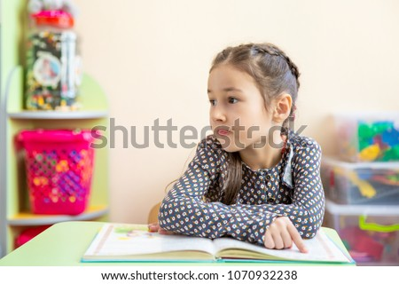 Cute little girl doing homework, reading a book, coloring pages, writing and painting. Children paint. Kids draw. Preschooler with books at home. Preschoolers learn to write and read. Creative toddler #1070932238