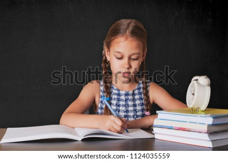 Cute little girl doing homework, reading a book, coloring pages, writing and painting. Children paint. Kids draw. Preschoolers learn to write and read. Creative toddler . #1124035559