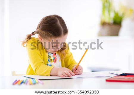 Cute little girl doing homework, reading a book, coloring pages, writing and painting. Children paint. Kids draw. Preschooler with books at home. Preschoolers learn to write and read. Creative toddler #554092330
