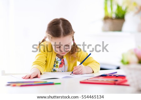 Cute little girl doing homework, reading a book, coloring pages, writing and painting. Children paint. Kids draw. Preschooler with books at home. Preschoolers learn to write and read. Creative toddler #554465134