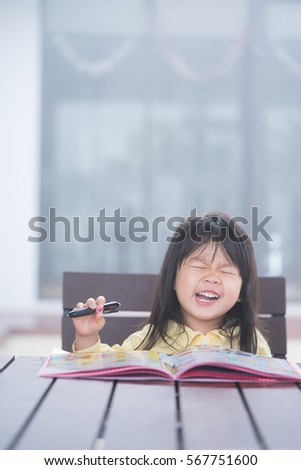 Cute little girl doing homework, reading a book, coloring pages, writing and painting. Children paint. Kids draw. Preschooler with books at home. Preschoolers learn to write and read. Creative toddler #567751600