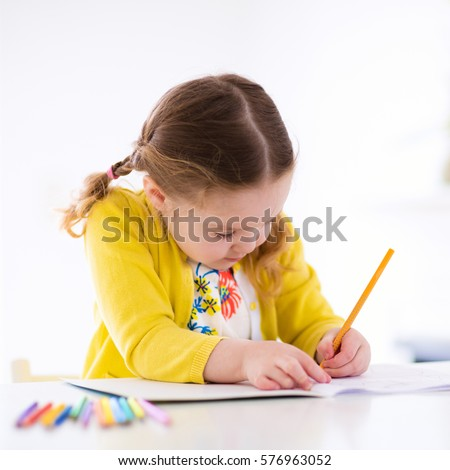 Cute little girl doing homework, reading a book, coloring pages, writing and painting. Children paint. Kids draw. Preschooler with books at home. Preschoolers learn to write and read. Creative toddler #576963052