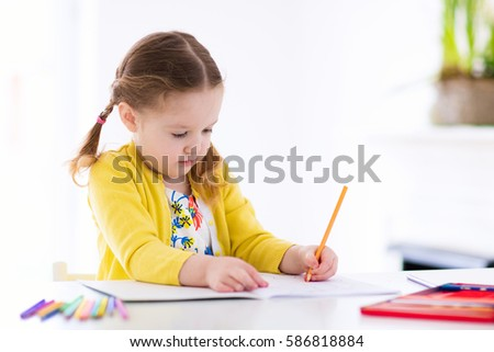 Cute little girl doing homework, reading a book, coloring pages, writing and painting. Children paint. Kids draw. Preschooler with books at home. Preschoolers learn to write and read. Creative toddler #586818884