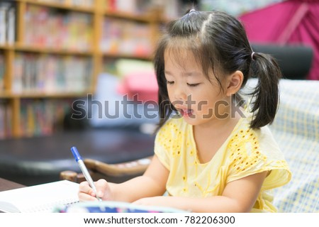 Cute little girl doing homework, reading a book, coloring pages, writing and painting. Children paint. Kids draw. Preschooler with books at home. Preschoolers learn to write and read.Creative toddler #782206300