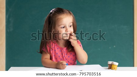Cute little girl doing homework, reading a book, coloring pages, writing and painting. Children paint. Kids draw. Preschooler with books at home. Preschoolers learn to write and read. Creative toddler #795703516