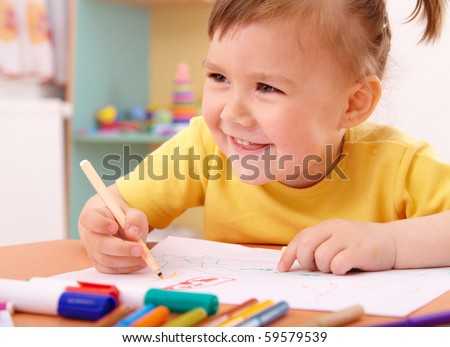 Cute little girl draw with felt-tip pen in preschool