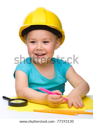 Cute little girl draw with marker wearing hard hat, isolated over white