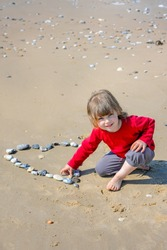cute little girl drawing a heart on the beach