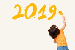 Cute little girl drawing new year 2019 with painting brush on wall background