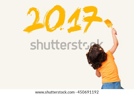 Cute little girl drawing new year 2017 with painting brush on wall background