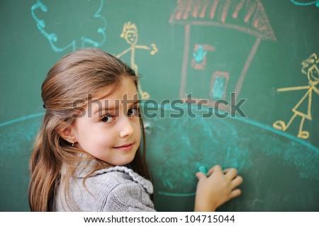 Cute little girl drawing on blackboard