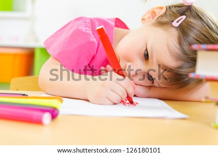 Cute little girl drawing with felt pen at home