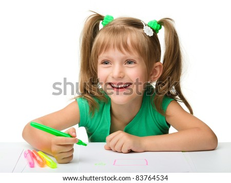 Cute little girl draws with markers while sitting at table, isolated over white
