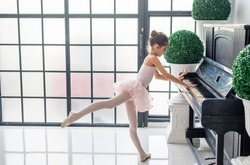 Cute little girl dreaming of becoming a ballerina. Child girl dancing and play piano in a pink tutu dancing on the stage. Girl is studying ballet.