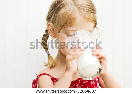 Cute little girl drinking a large glass of milk