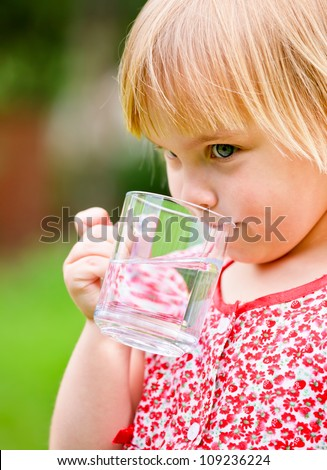 Cute little girl drinking water outdoors