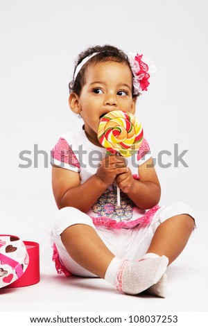 Cute little girl eating a big lollipop - stock photo