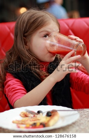 Cute little girl eating and drinking juice in cafe