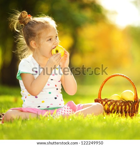 Cute little girl eating apple in the park