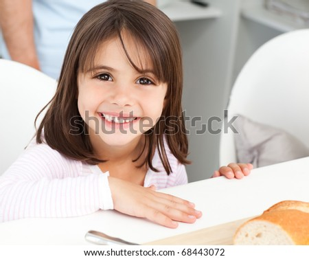 Cute little girl eating bread during breakfast in the kitchen