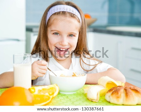 cute little girl eating cereal with the milk in the kitchen