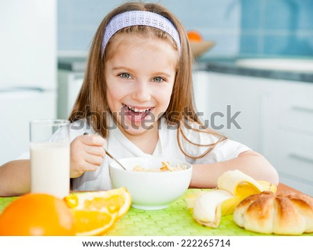 cute little girl eating cereal with the milk in the kitchen #222265714