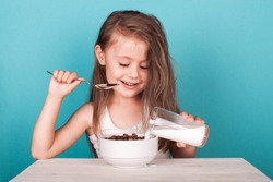 Cute little girl eating chocolate cereal with milk for breakfast