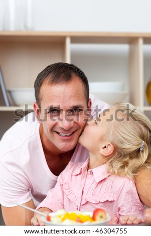 Cute little girl eating fruit with her father in the kitchen