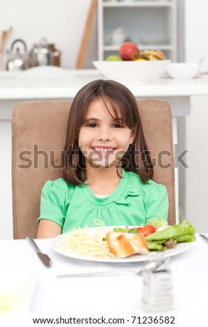 Cute little girl eating pasta and salad in the kitchen