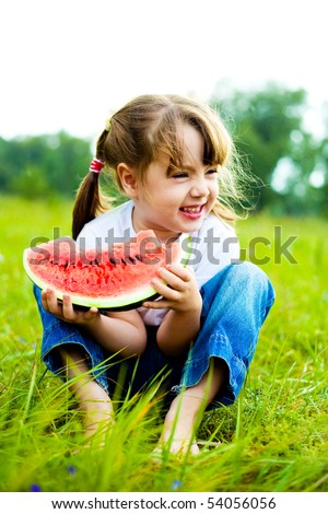 cute little girl eating  water-melon on the grass in summertime