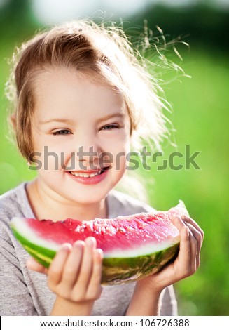 cute little girl eating watermelon in the summer park