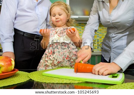 Cute little girl eats carrot and apples in kitchen - stock photo