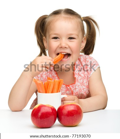 Cute little girl eats carrot and apples, isolated over white - stock photo