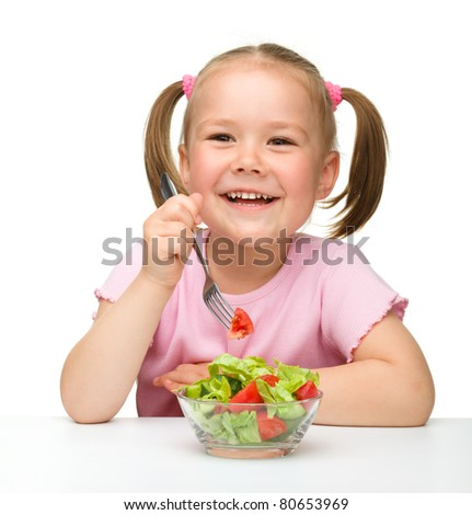 Cute little girl eats vegetable salad using fork, isolated over white