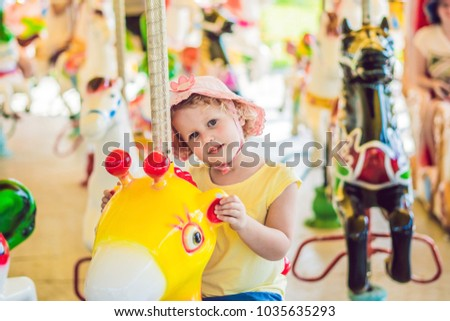 Cute little girl enjoying in funfair and riding on colorful carousel house