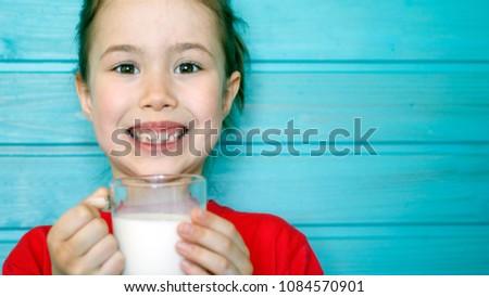 Cute little girl enjoys the taste of fresh milk #1084570901