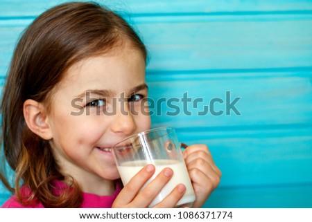 Cute little girl enjoys the taste of fresh milk #1086371774