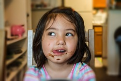 cute little girl feeling happy and getting messy face while eating chocolate in dining room with blurred background