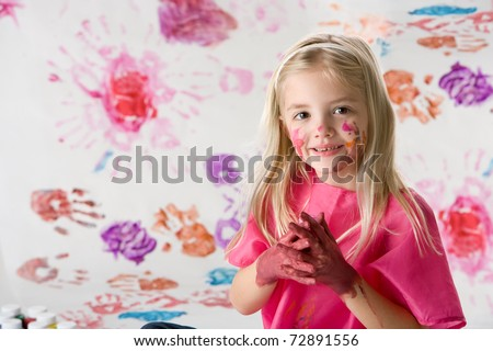 Cute little girl finger painting isolated on white background
