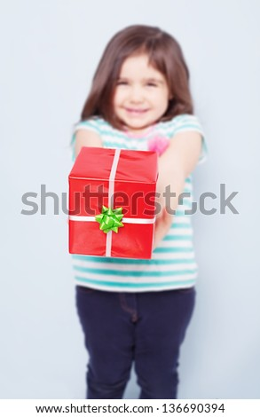cute little girl giving you a red gift box on blue background.