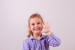 Cute little girl happily shows an open hand, five fingers Emotion