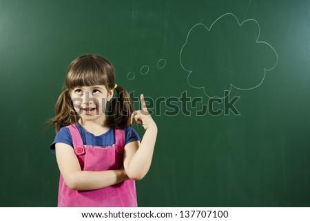 Cute little girl has an idea in front of blackboard,Little girl with an idea