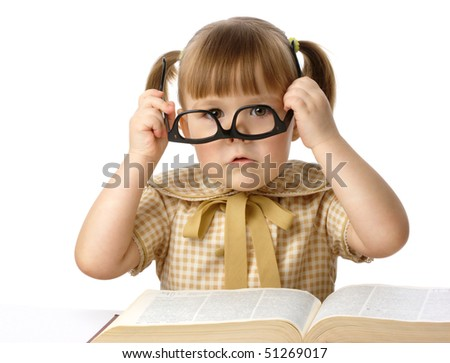 Cute little girl having fun with big book wearing black glasses, back to school concept, isolated over white