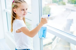 Cute little girl helping parents with cleaning the window with spray